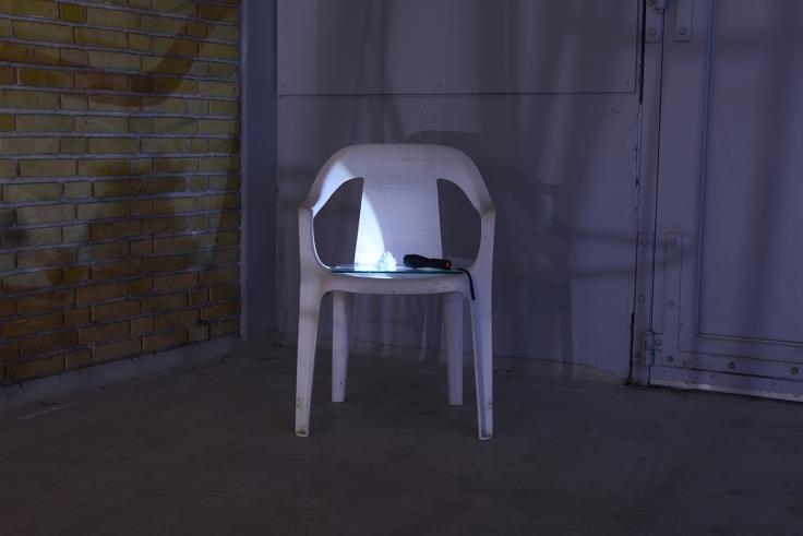 12.Kontakt 2018. Plastik havestol, glasplade a╠ü 25x25cm, lommelygte og brugte kontaktlinser. Belysning af indt├©rrede kontaktlinser indsamlet gennem en a╠èrr├ªkke. Foto af H